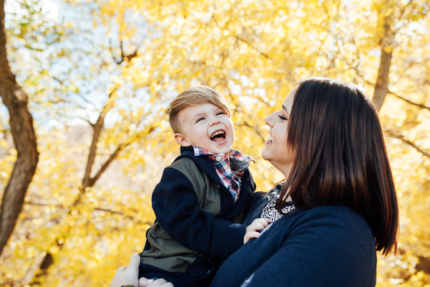 candid-photo-of-mother-and-son-laughing-in-fall-leaves-during-free-mini-session-with-jen-farichild-photography-in-salt-lake-city-utah