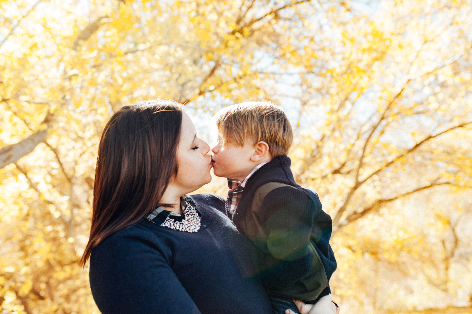 mother-and-son-kissing-in-fall-leaves-with-jen-fairchild-photography-slc-utah