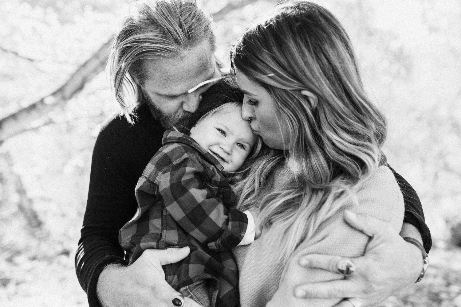 black-and-white-intimate-photo-of-parents-kissing-child-salt-lake-city-utah