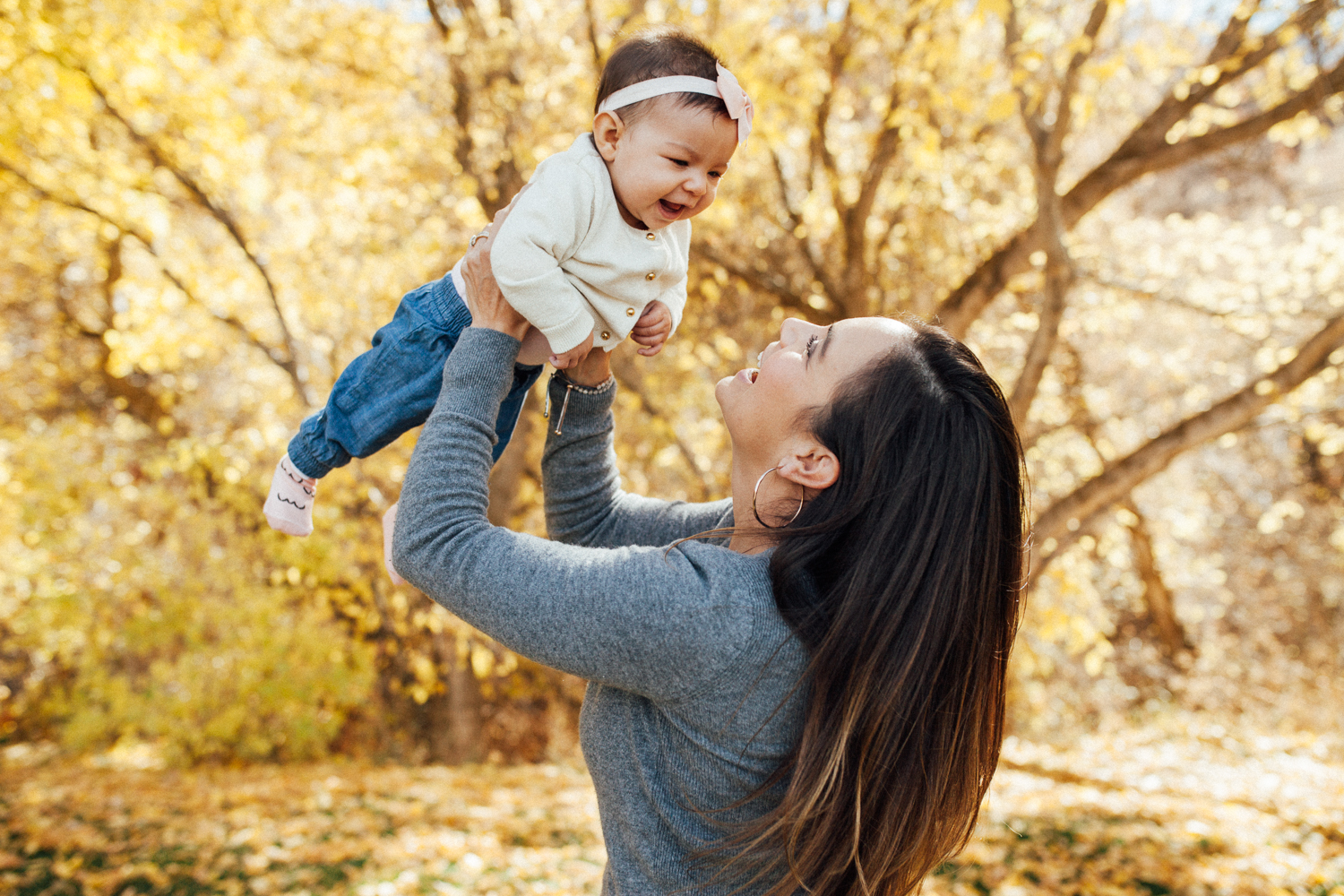 mother-holding-baby-girl-in-air-fall-leaves-rotary-geln-park-slc-ut