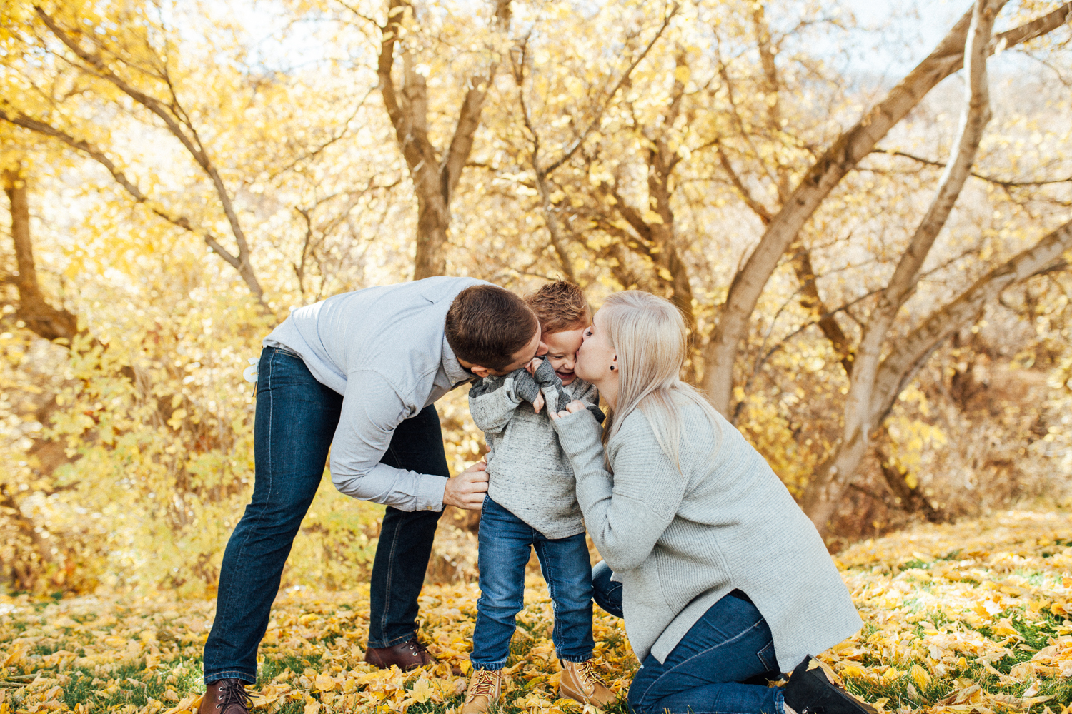 candid-family-photo-of-mother-and-father-kissing-toddler-in-fall-leaves-at-rotary-glen-park-in-salt lake city-utah