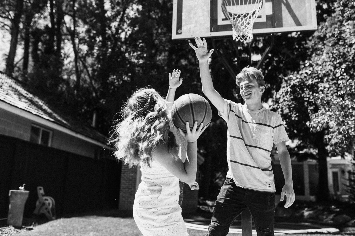 candid-photo-of-boy-and-girl-playing-basketball-during-at-home-photo-session-with-jenfairchild-photography-slc-ut