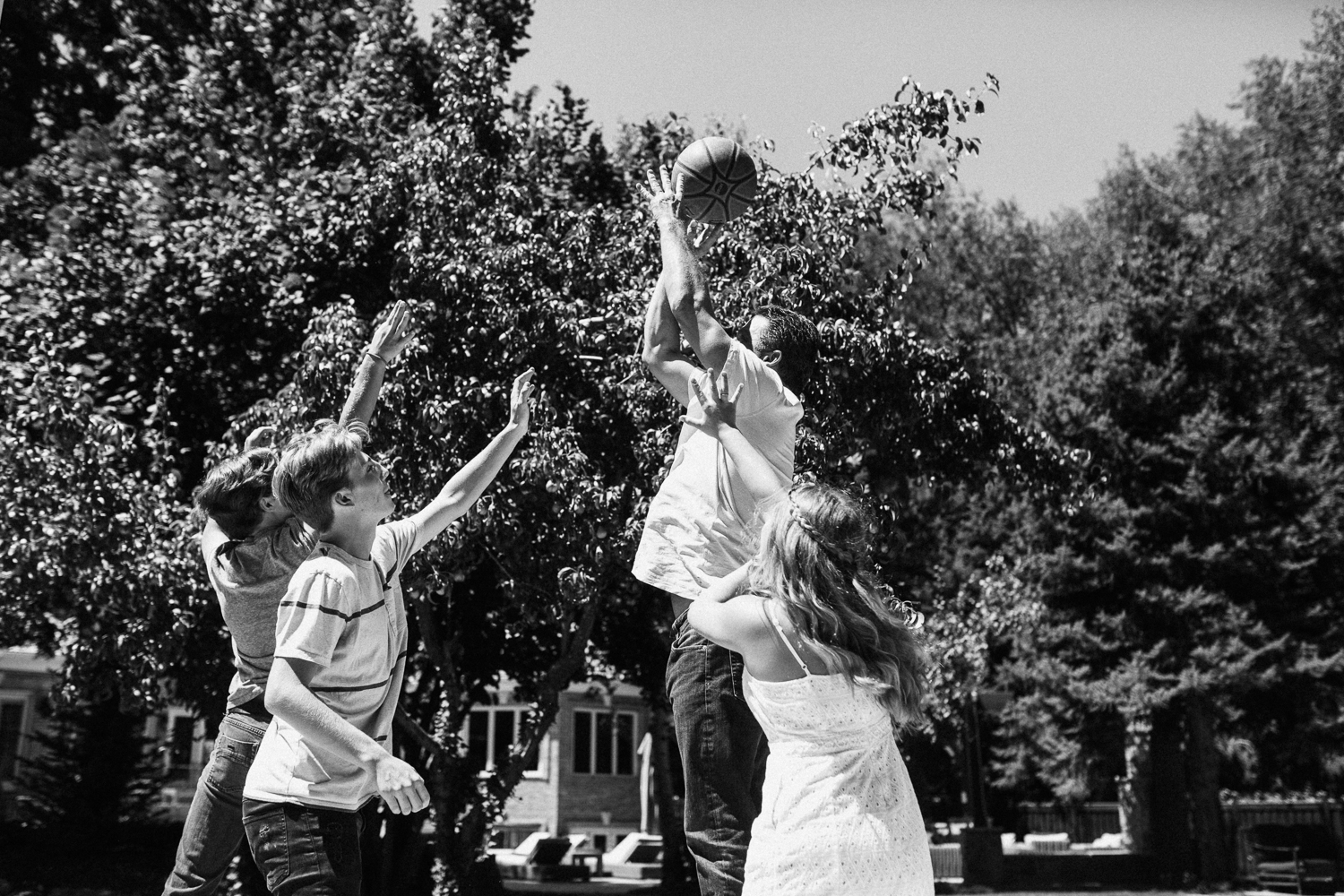 candid-black-and-white-photo-of-father-and-children-playing-basketball-at-home-with-jen-fairchild-photography-in-slc-ut