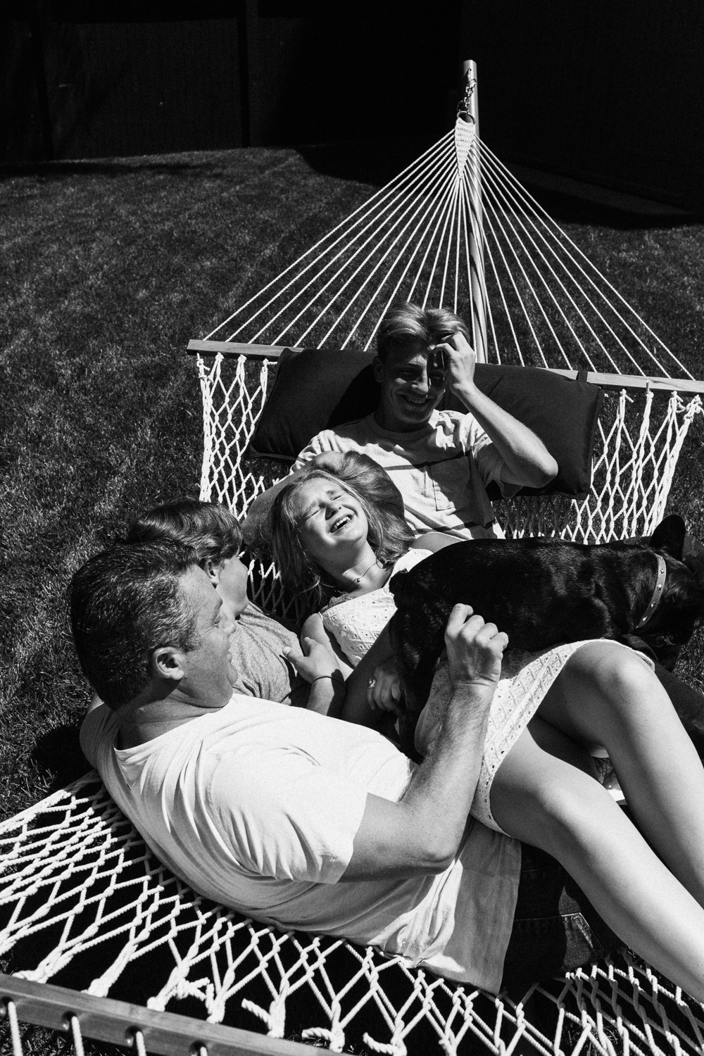 candid-black-and-white-photo-of-family-laughing-together-on-hammock-slc-ut