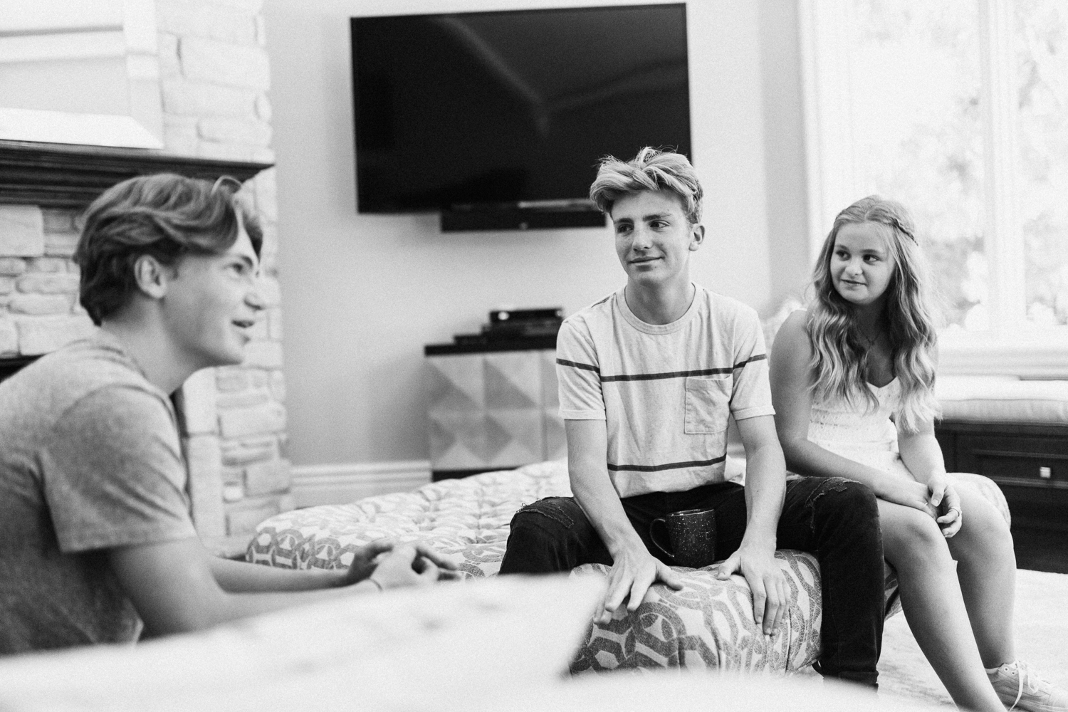 candid-black-and-white-photo-of-siblings-conversating-in-living-room-during-in-home-session-with-jen-fairchild-photography-in-salt-lake-city-ut