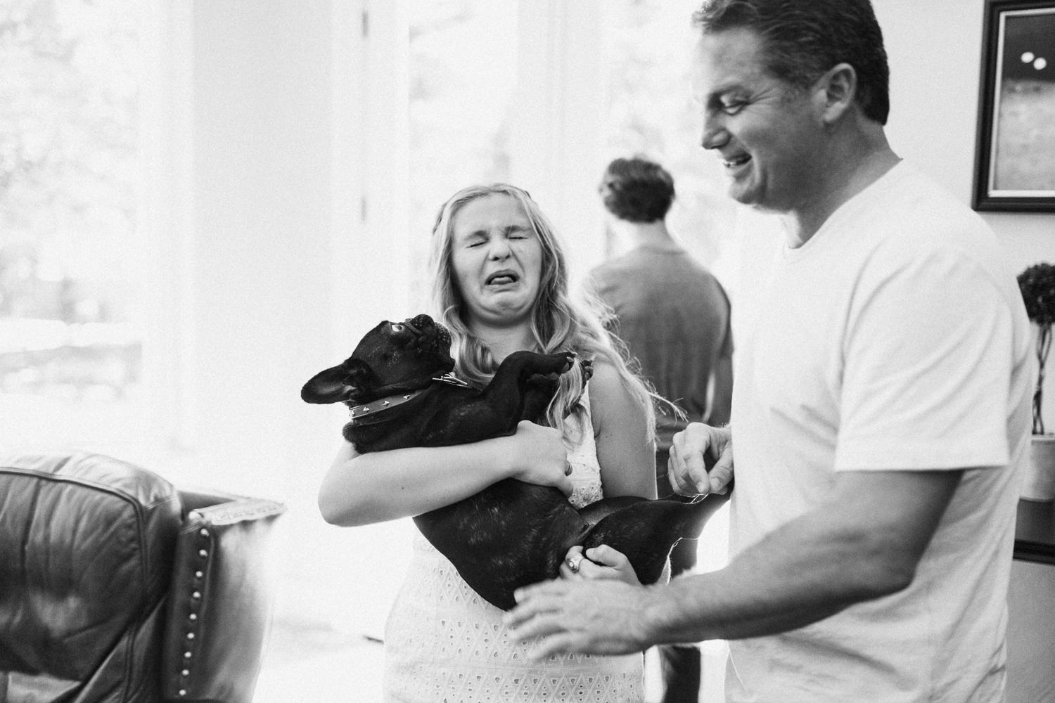 candid-photo-of-girl-making-funny-face-while-holding-pug-dog-with-father-during-in-home-session-with-jen-fairchild-photography-in-salt-lake-city-utah
