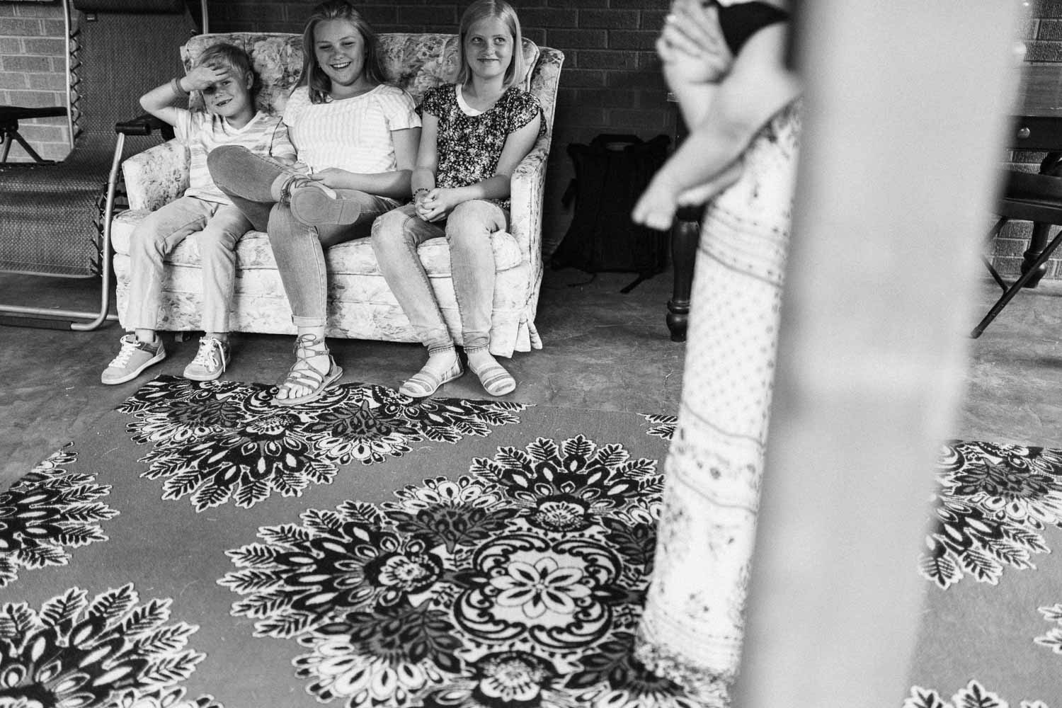 black-and-white-artistic-photo-of-three-girls-sitting-on-couch-in-back-yard-salt-lake-city-utah