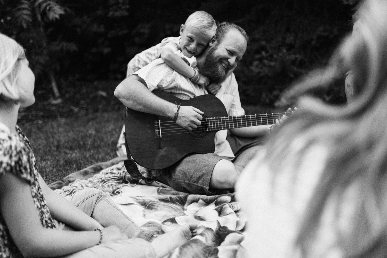 candid-black-and-white-photo-of-father-and-sun-hugging-and-playing-guitar-salt-lake-city-utah