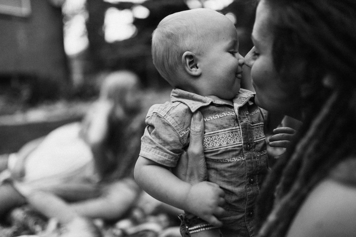 black-and-white-candid-photo-of-mother-kissing-son-slc-utah