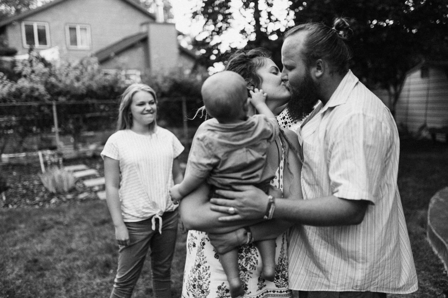 candid-black-and-white-family-photo-parents-kissing-in-backyard-during-in-home-session-with-jen-fairchild-in-slc-utah