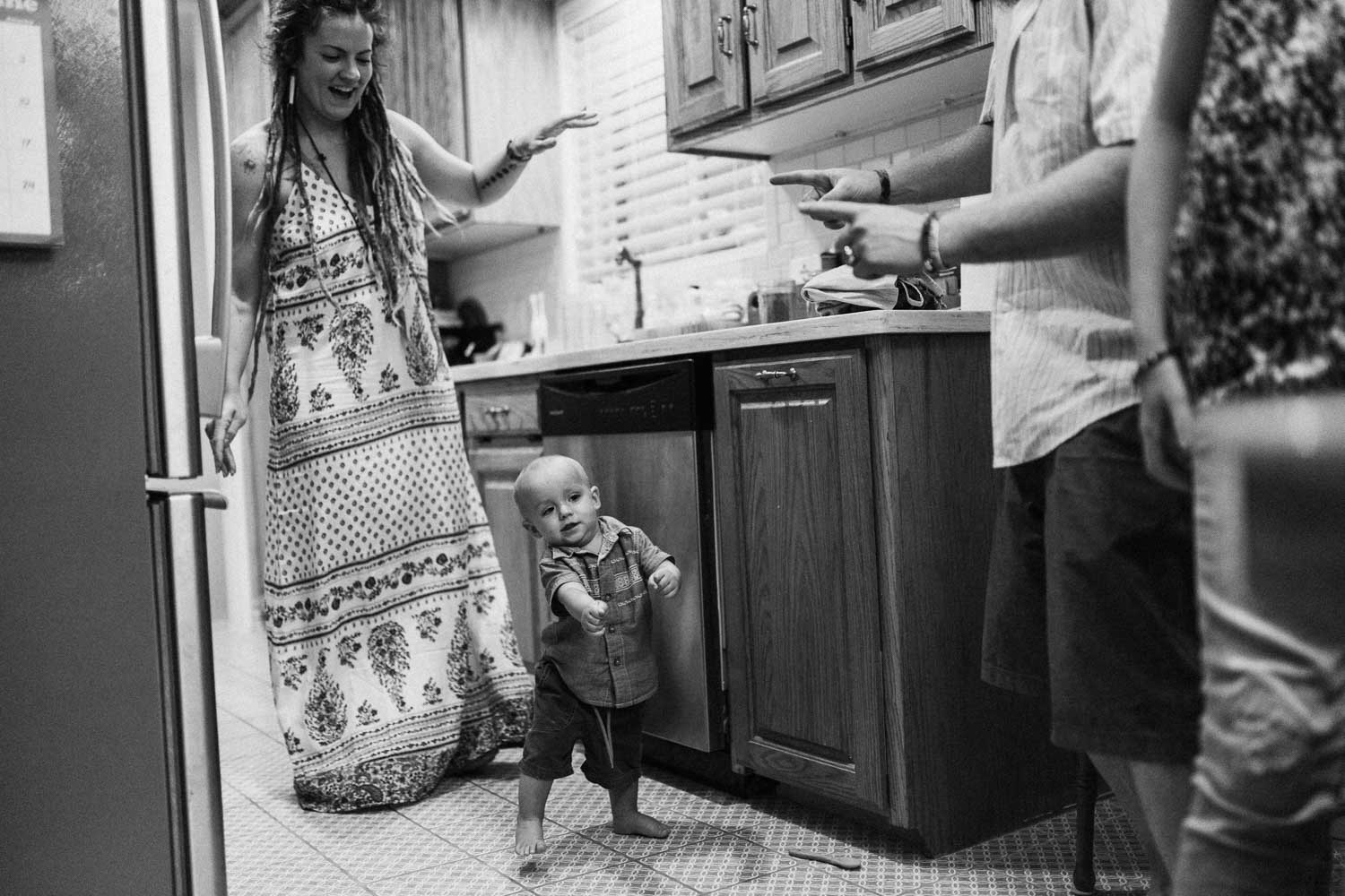 black-and-white-candid-photo-baby-walking-in-kitchen-salt-lake-ut