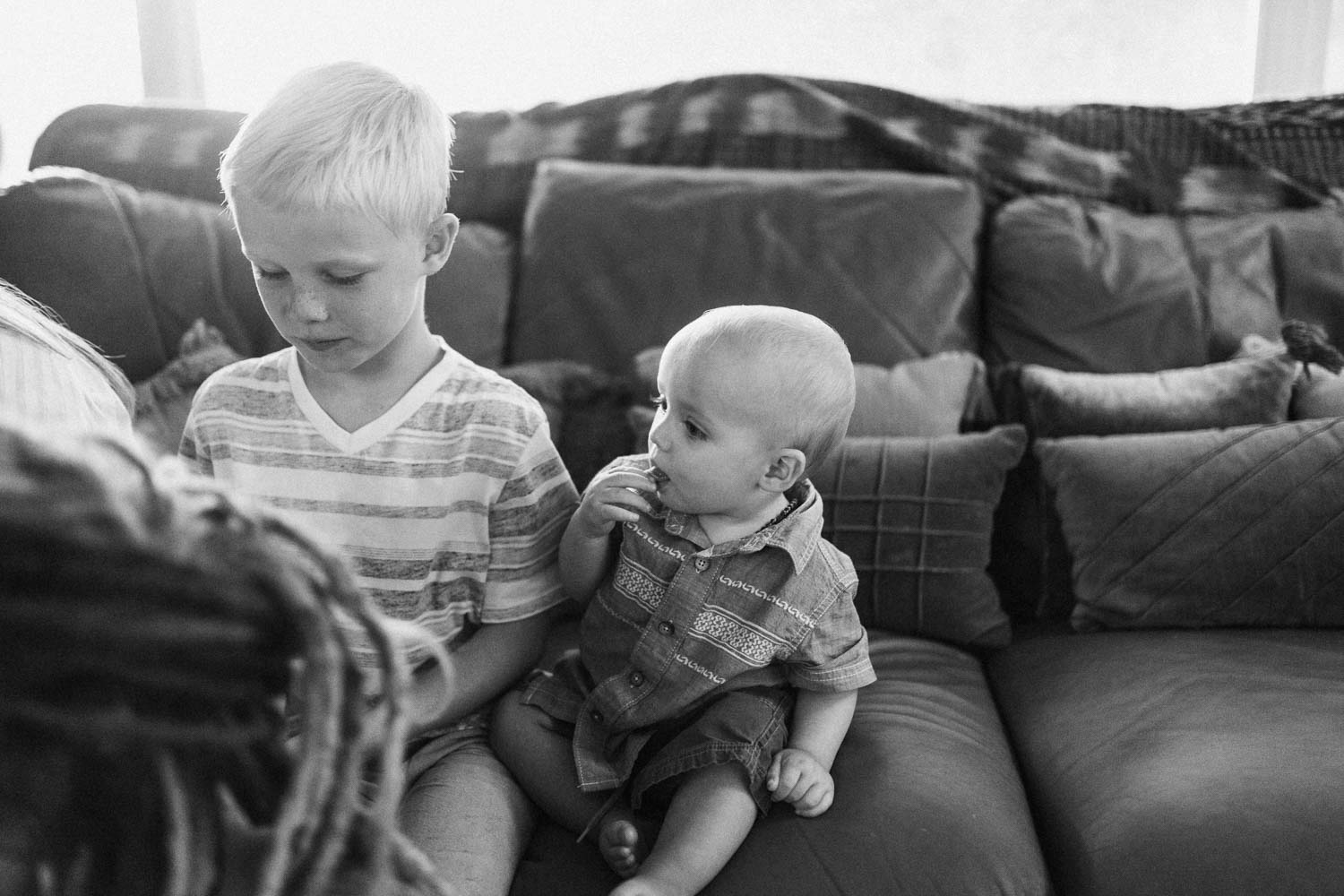candid-black-and-white-photo-of-brothers-sitting-on-couch-for-story-time-salt-lake-city-utah