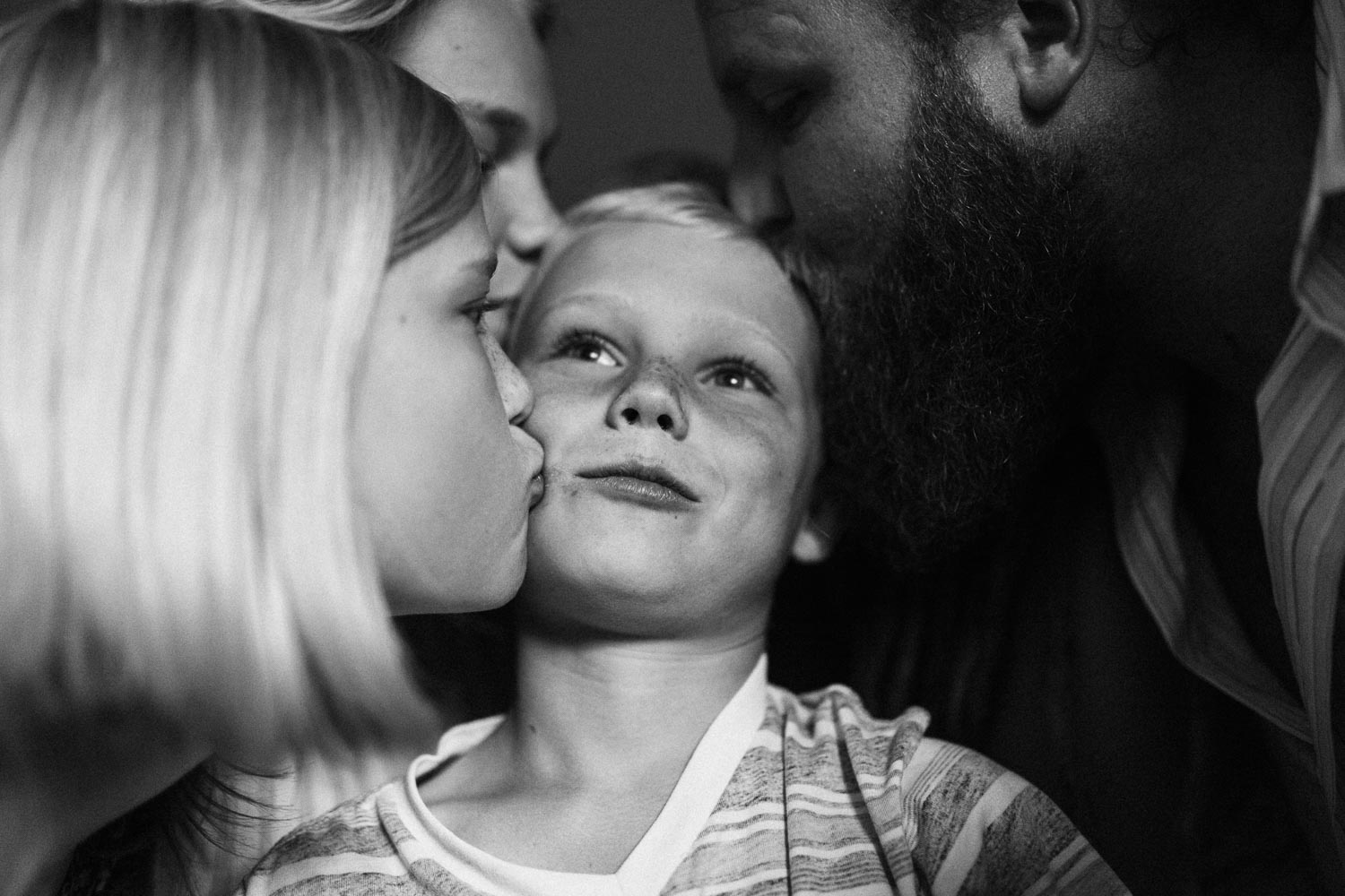 candid-black-and-white-family-photo-kissing-little-brother-during-in-home-session-with-jen-fairchild-in-salt-lake-city-utah