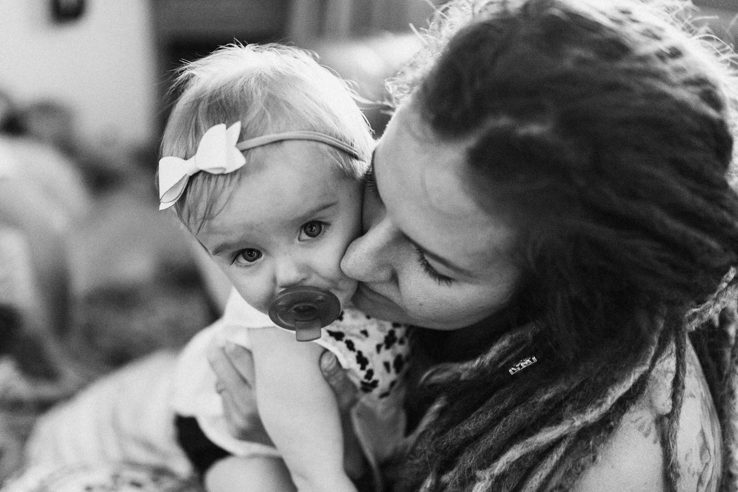 candid-black-and-white-photo-little-girl-looking-at-camera-with-binky-during-in-home-session-with-jen-fairchild-in-salt-lake-city-utah