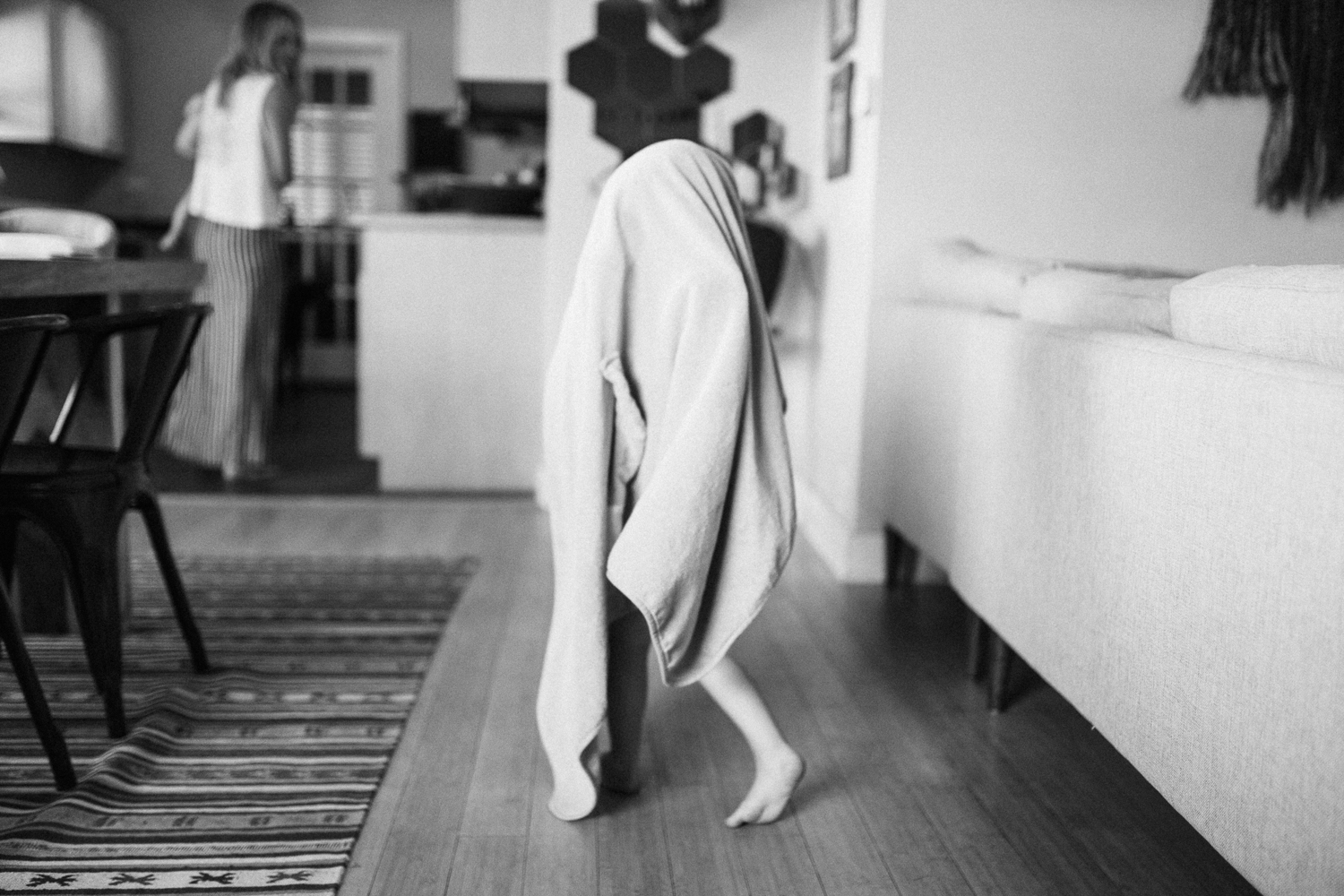 candid-and-natural-black-and-white-girl-under-blanket-dancing-in-kitchen-slc-utah