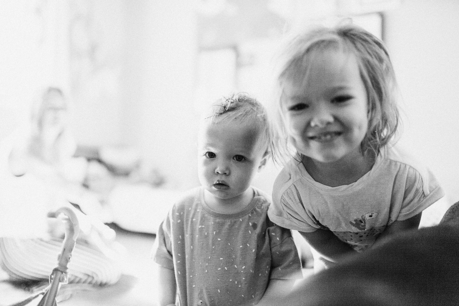 candid-black-and-white-photo-little-girls-looking-at-camera-with-binky-during-in-home-session-with-jen-fairchild-in-salt-lake-city-utah