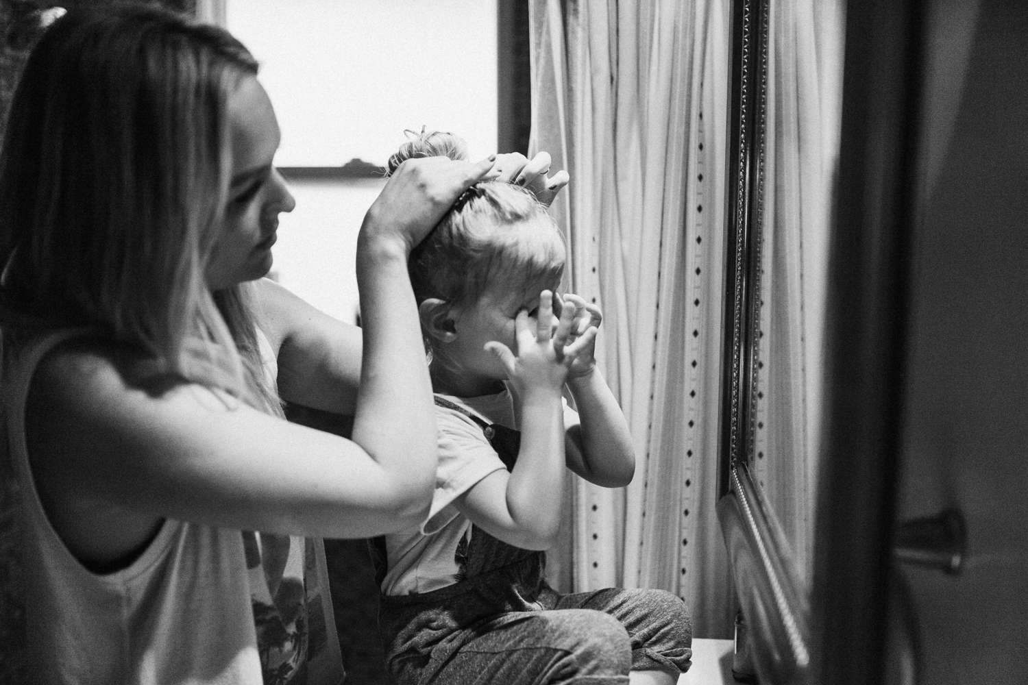 black-and-white-candid-photo-of-mother-doing-dauhgers-hair-during-in-home-session-with-jen-fairchild-photography-slc-ut