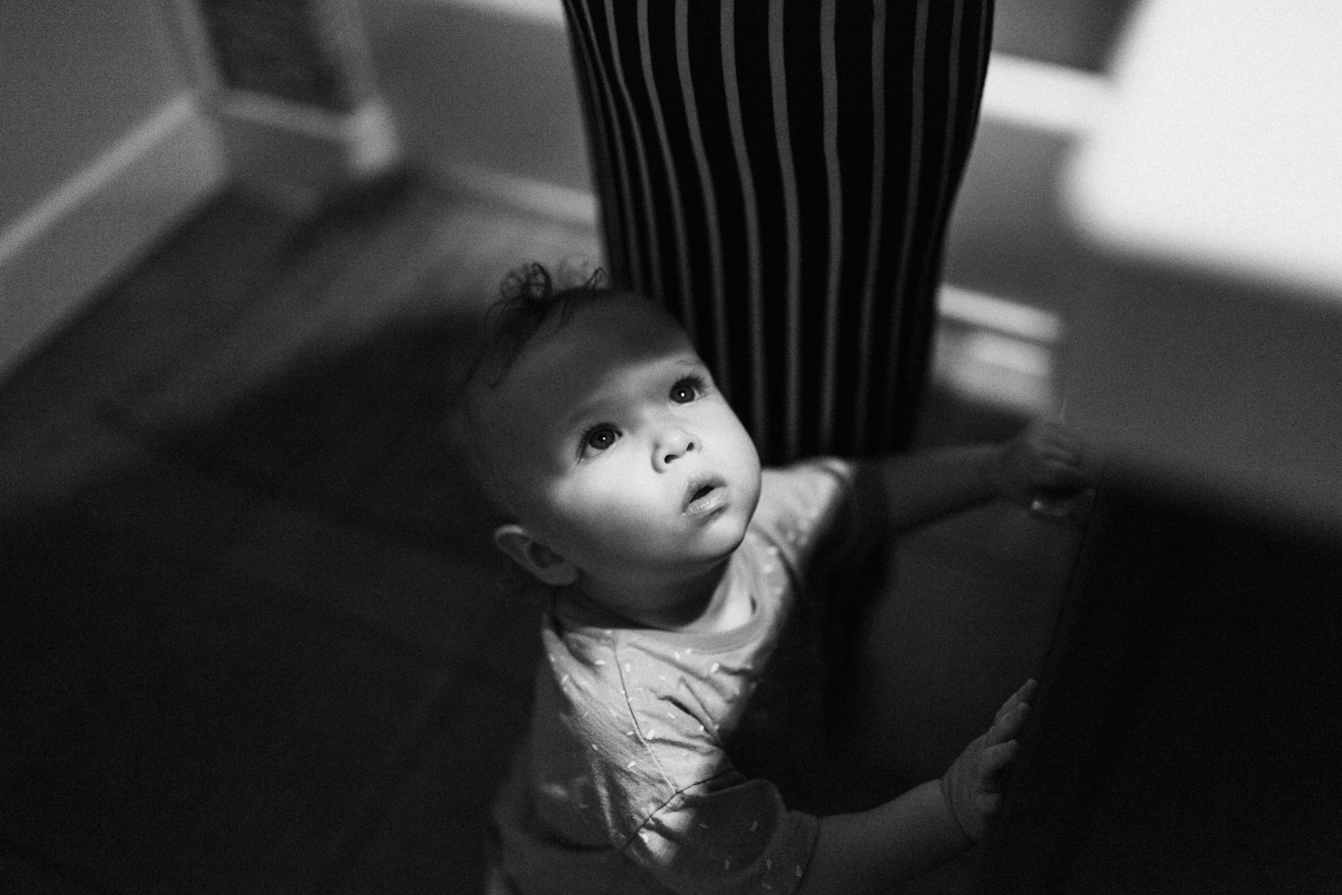 candid-black-and-white-photo-little-girl-looking-up-at-mom-with-during-in-home-session-with-jen-fairchild-in-salt-lake-city-utah