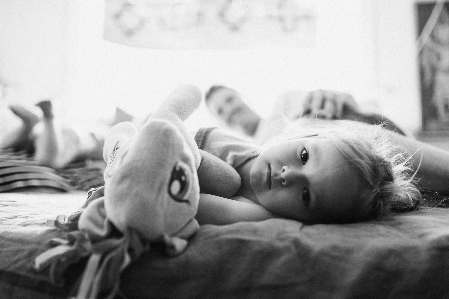 candid-black-and-white-photo-little-girl-looking-at-camera-with-unicorn-during-in-home-session-with-jen-fairchild-in-salt-lake-city-utah