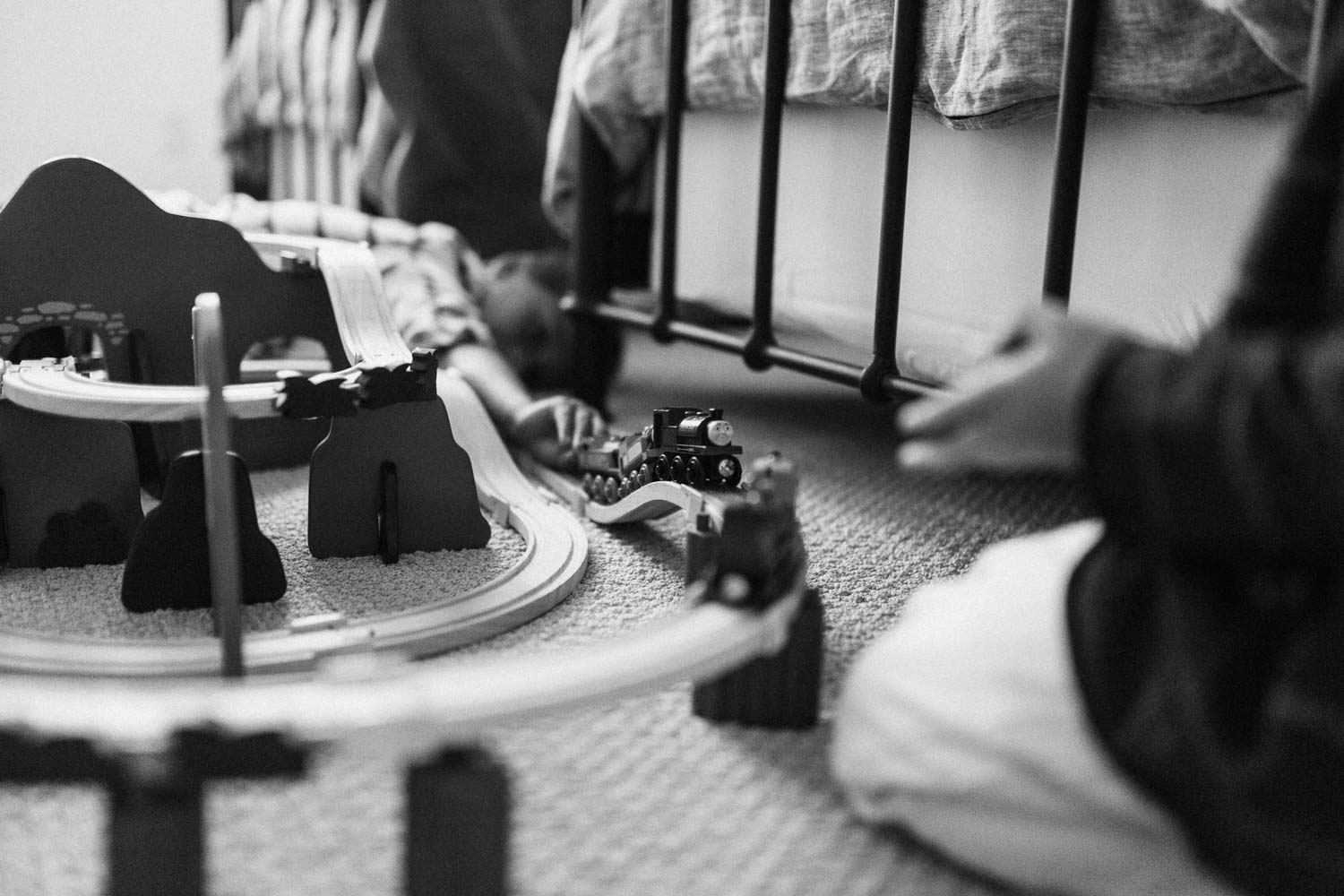 candid-black-and-white-photo-of-boys-playing-with-wooden-train-track-during-in-home-session-with-jen-fairchild-photography-in-encinitas-california