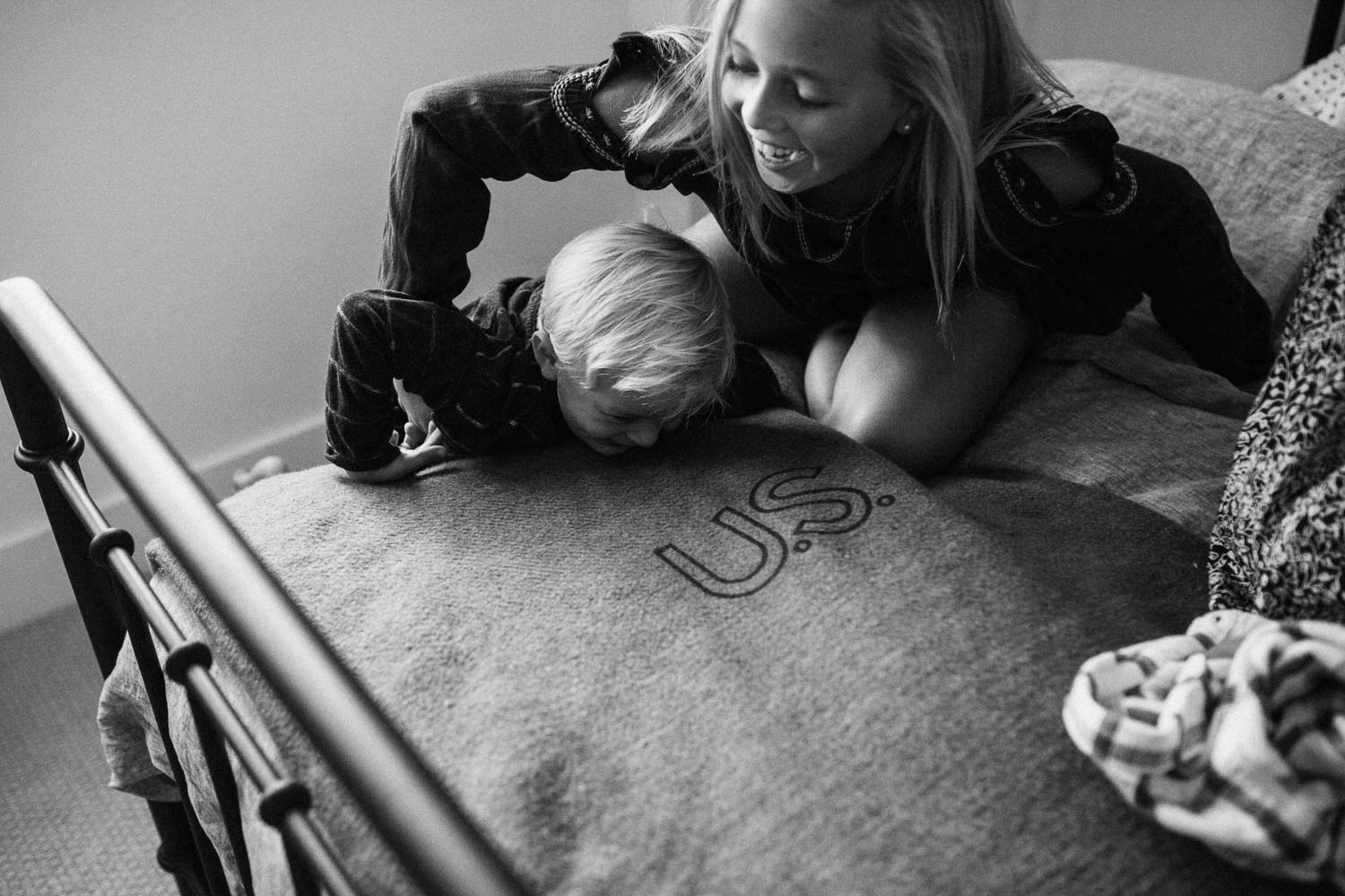 candid-black-and-white-photo-of-sister-helping-brother-up-onto-bed-eniciniats-ca
