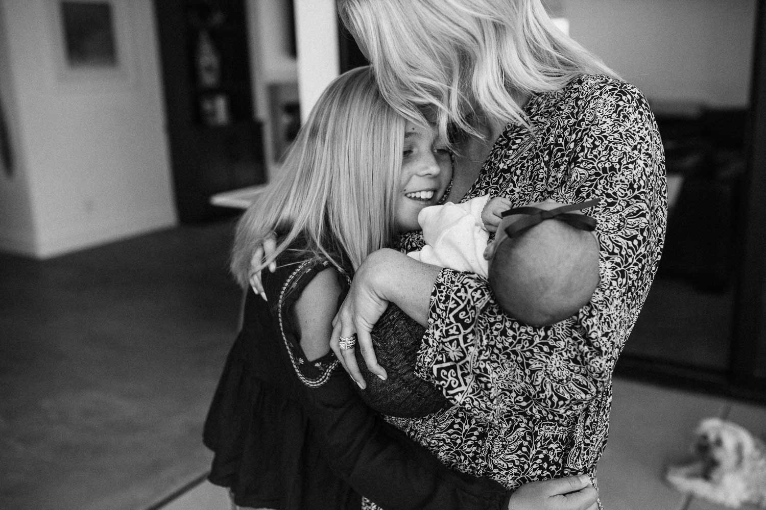 candid-black-and-white-photo-of-mother-hugging-daughters-during-in-home-session-with-jen-fairchild-photography-in-encinitas-california