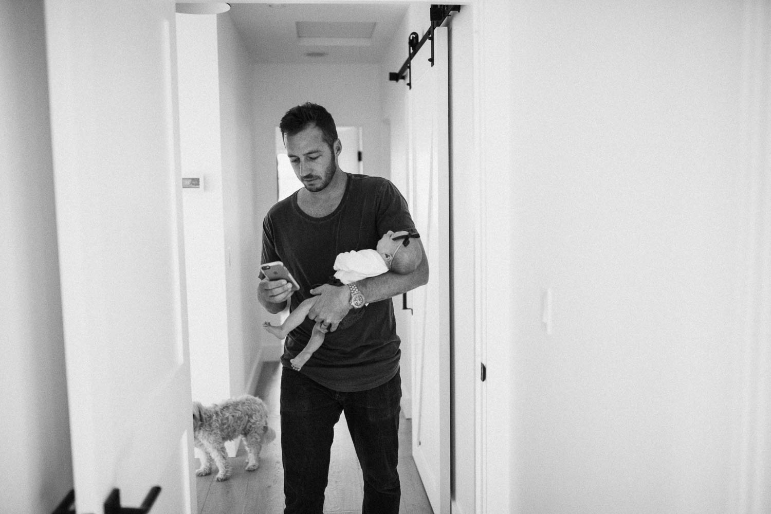 candid-black-and-white-photo-of-father-carrying-baby-in-hallway-of-home-encinita-california