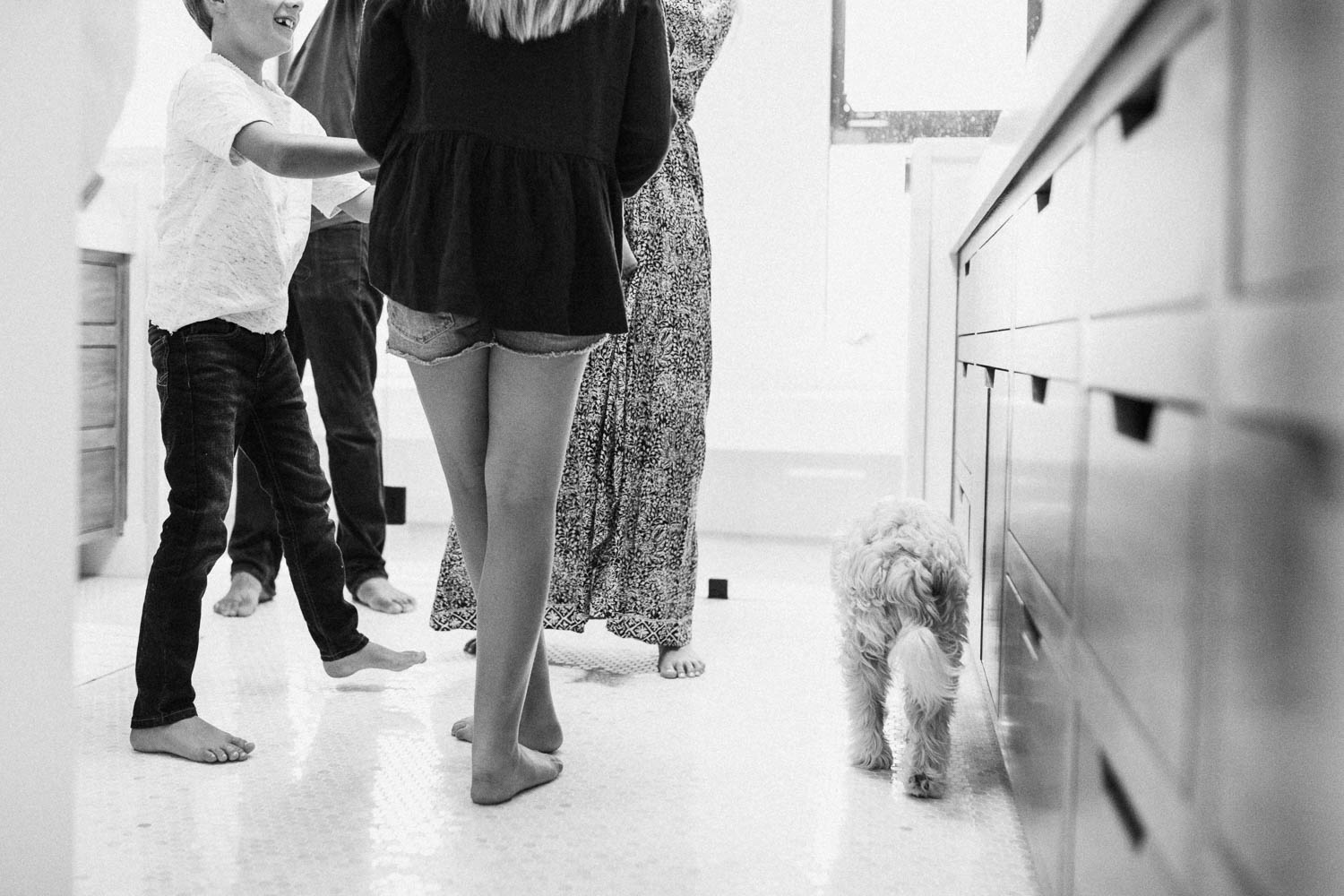 candid-and-artistic-photo-in-bathroom-of-families-legs-and-dog-encinita-ca