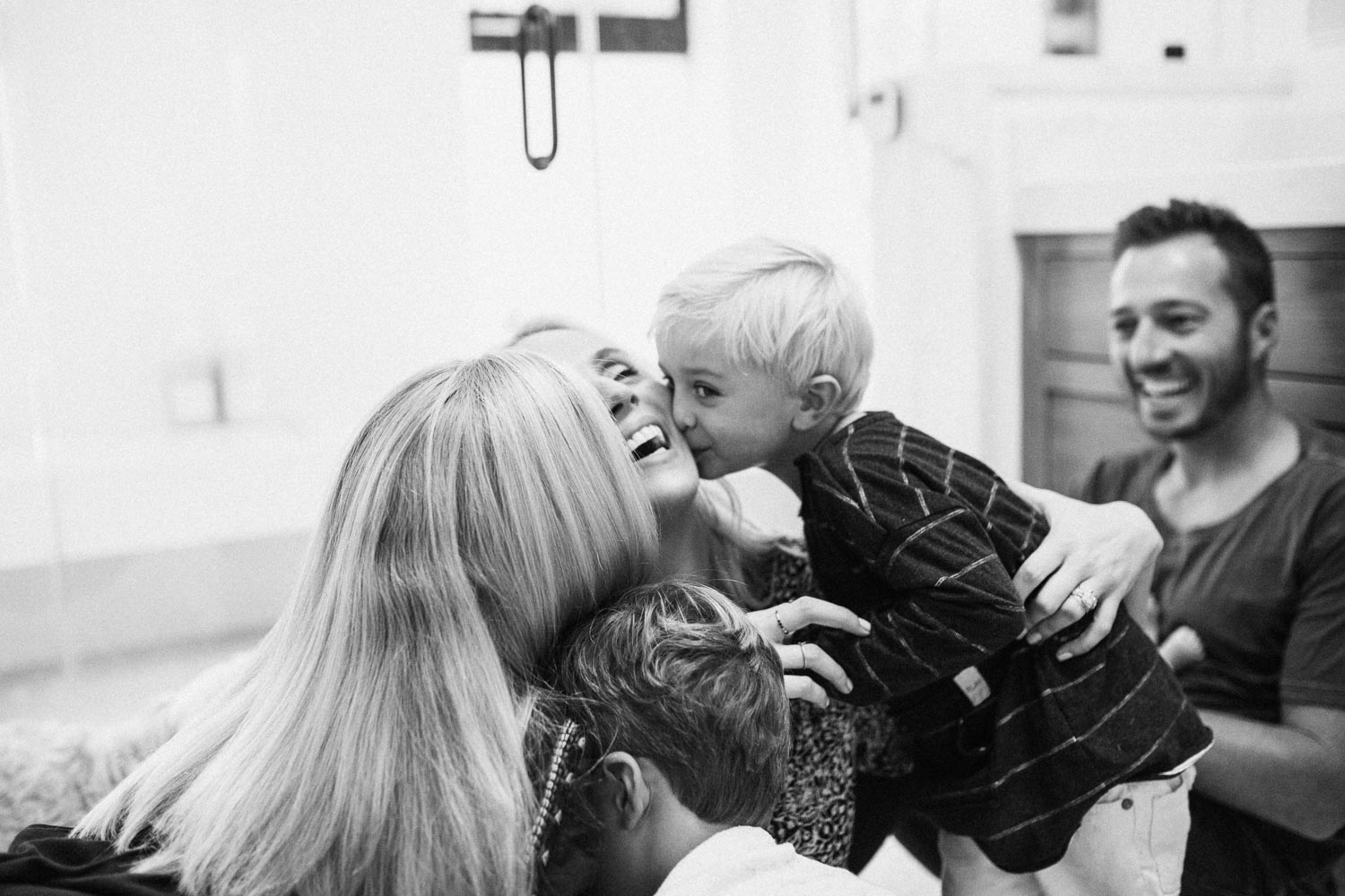 candid-black-and-white-family-photo-kissing-mom-during-in-home-session-with-jen-fairchild-in-encinita-ca