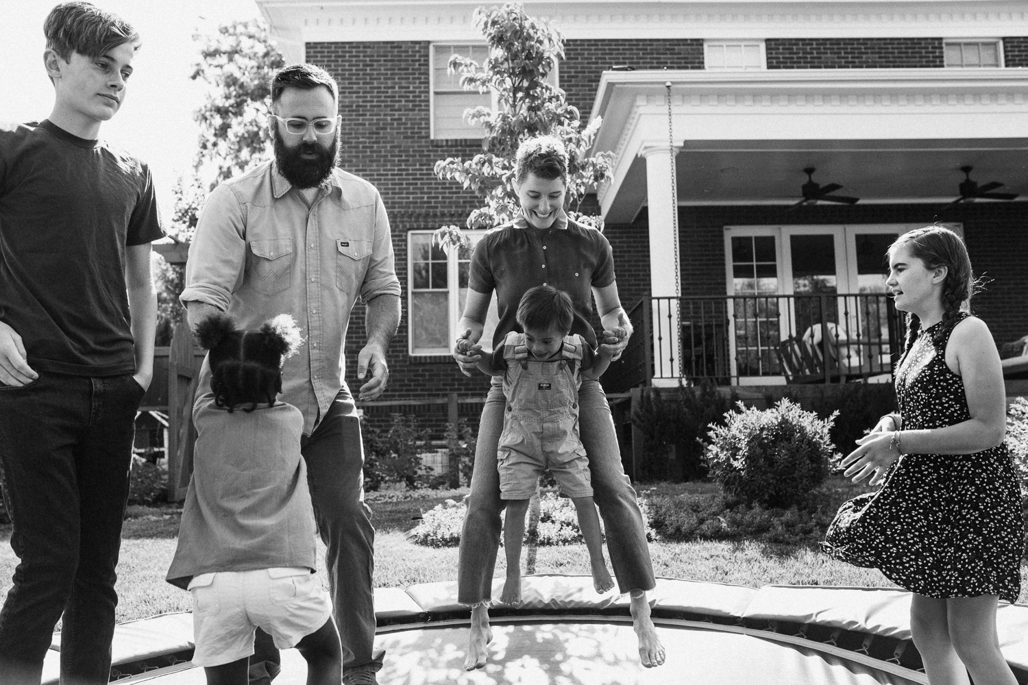 candid-black-and-white-family-photo-jumping-on-trampoline-during-in-home-session-with-jen-fairchild-in-salt-lake-city-utah