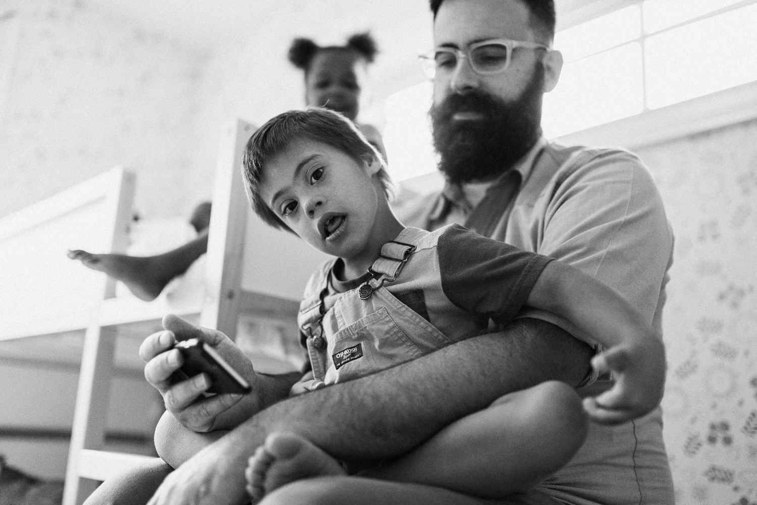 candid-black-and-white-photo-of-son-sitting-on-fathers-lap-during-in-home-session-with-jen-fairchild-in-salt-lake-city-utah