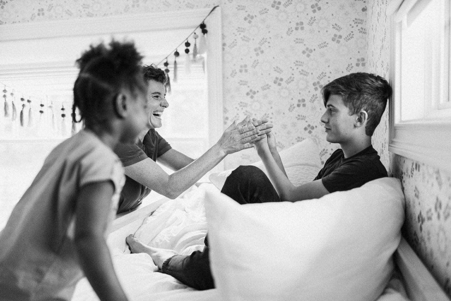 candid-black-and-white-photo-of-siblings-playing-on-bed-during-in-home-session-with-jen-fairchild-in-salt-lake-city-utah