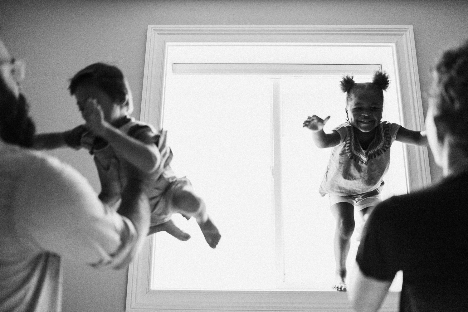 natural-and-artistic-black-and-white-photo-of-brother-and-sister-jumping-off-window-sill-into-parents-arms-salt-lake-utah