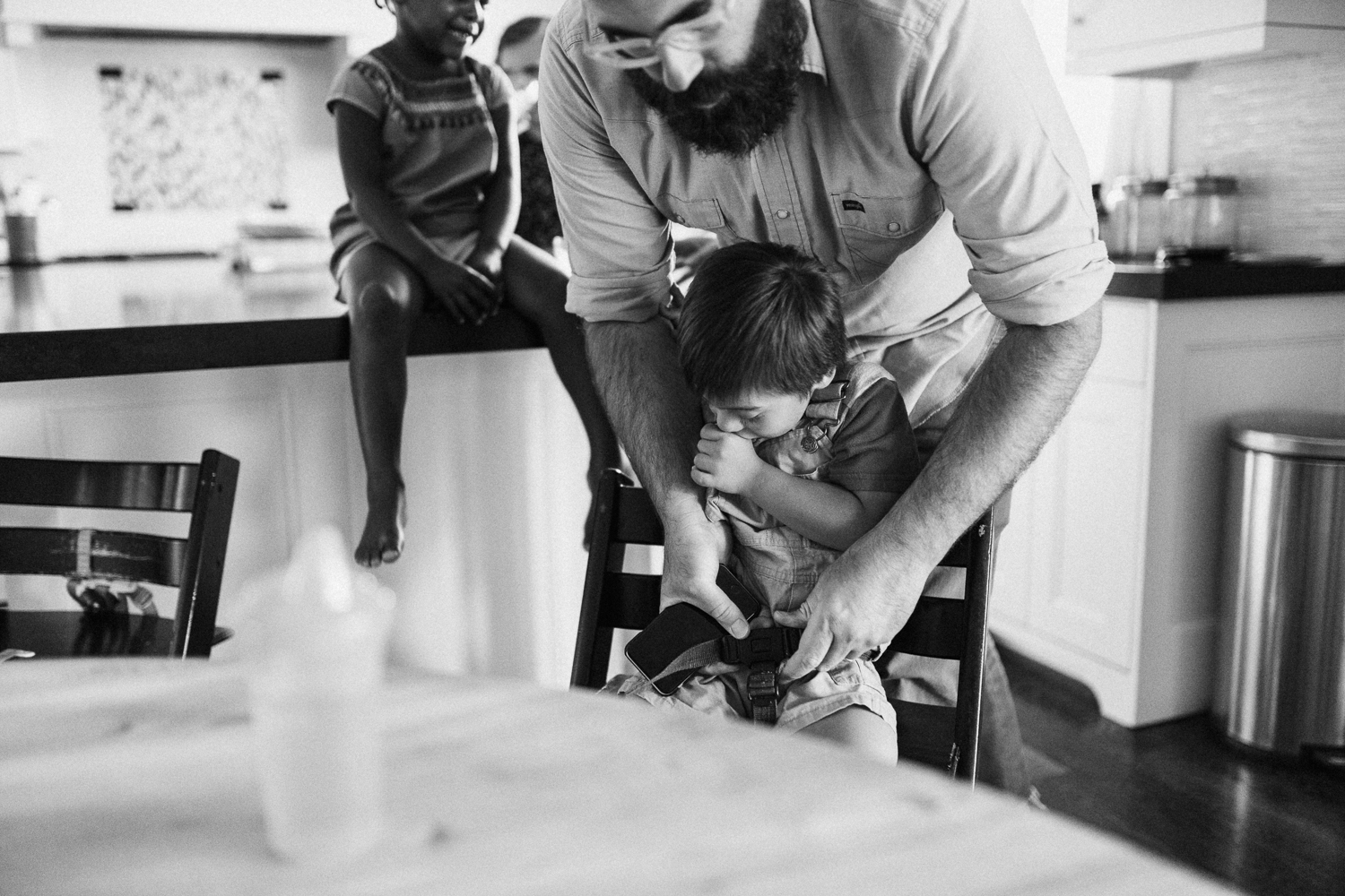natural-and-artistic-photo-father-buckling-son-into-highchair-slc-ut