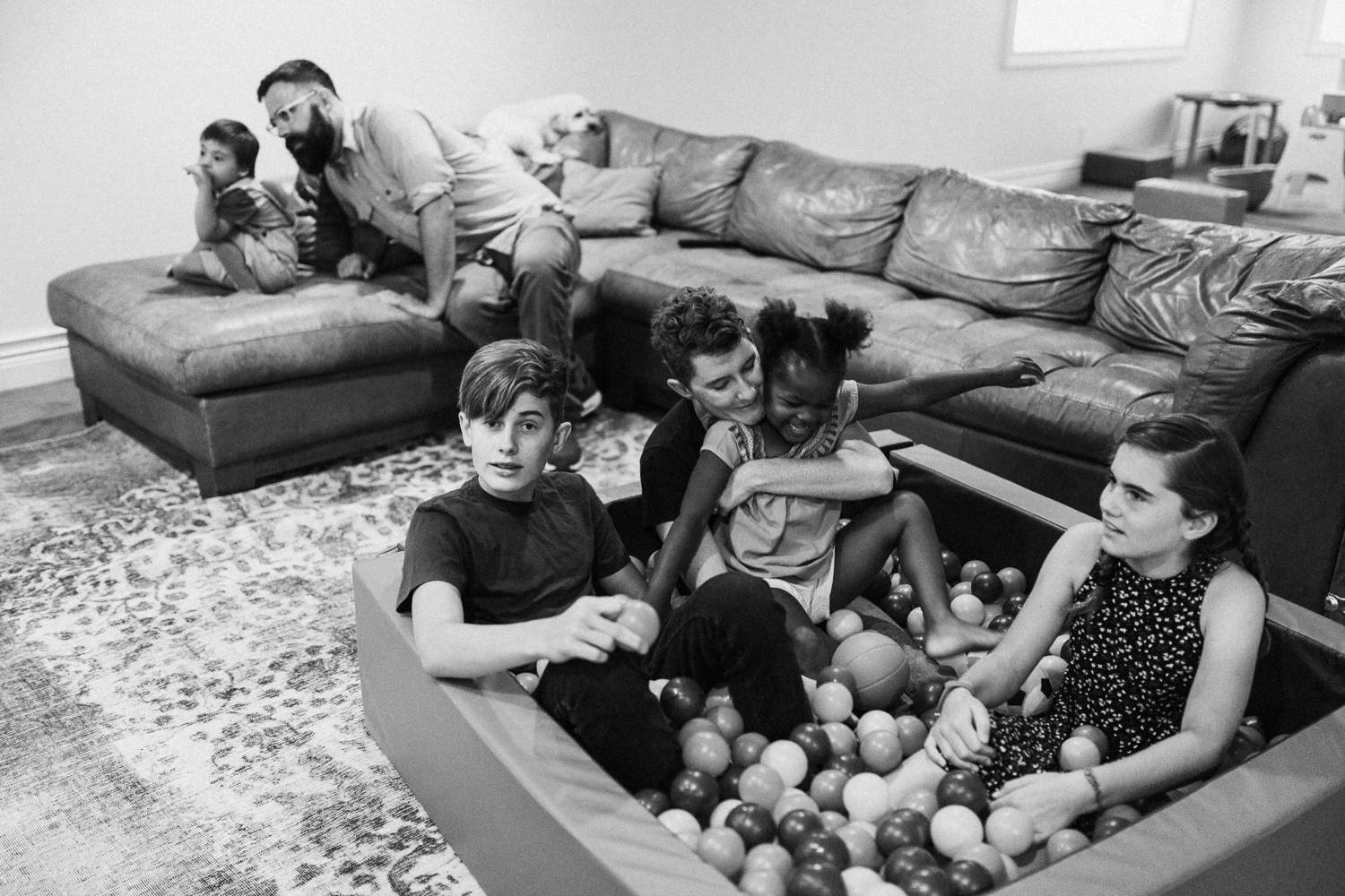 candid-black-and-white-family-photo-in-play-pin-of-plastic-balls-during-in-home-session-with-jen-fairchild-in-salt-lake-city-utah