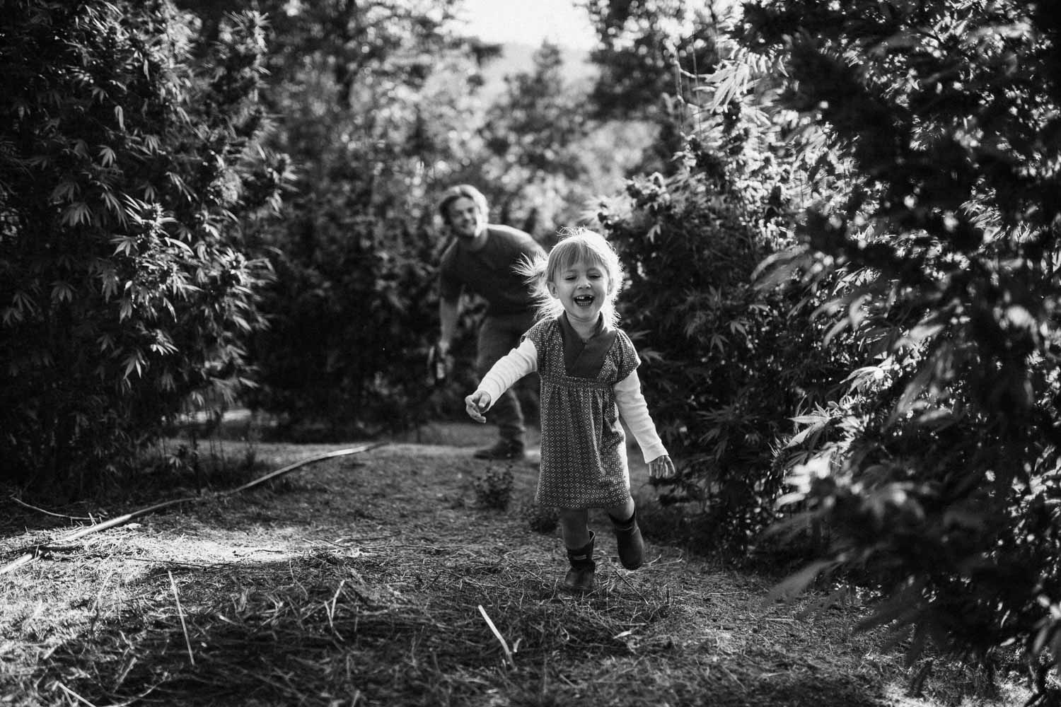 candid-black-and-white-photo-of-little-girl-running-through-weed-farm-in-sanfrancisco-cali
