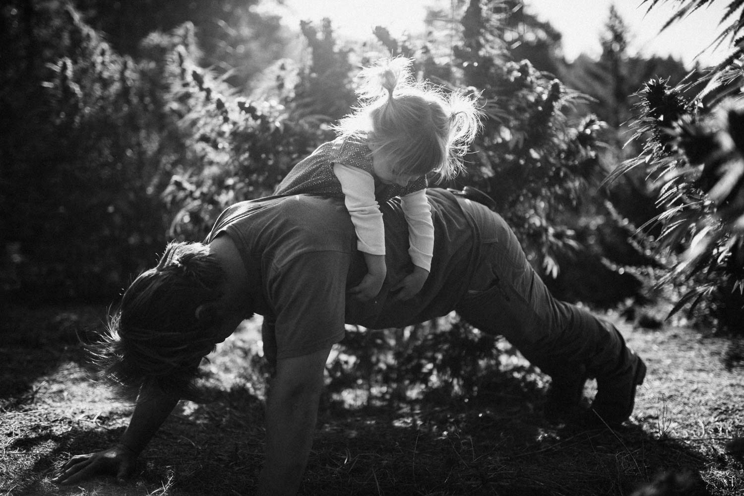 natural-and-artistic-black-and-white-photo-of-boy-doing-push-ups-with-little-girl-on-his-back-on-weed-farm-in-benbow-california