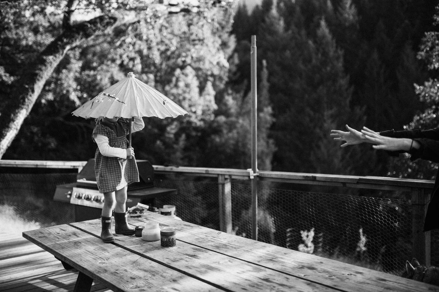 natural-and-artistic-black-and-white-emotional-image-dancing-on-picnic-table-with-unbrella-during-at-home-session-with-jen-fairchild-photography-garberville-ca