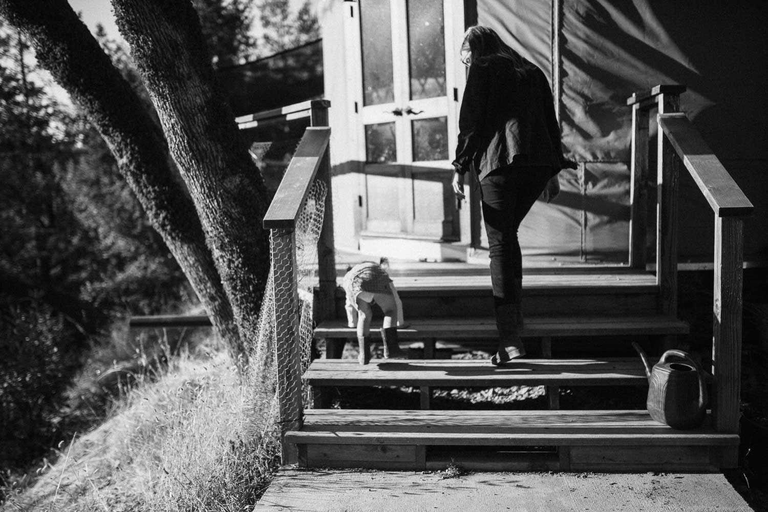 candid-black-ad-white-image-of-mother-and-daughter-walking-into-home-benbow-california