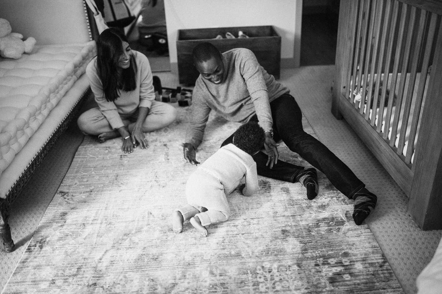 candid-black-and-white-photo-of-parents-laughing-and-playing-on-floor-with-child-la-california