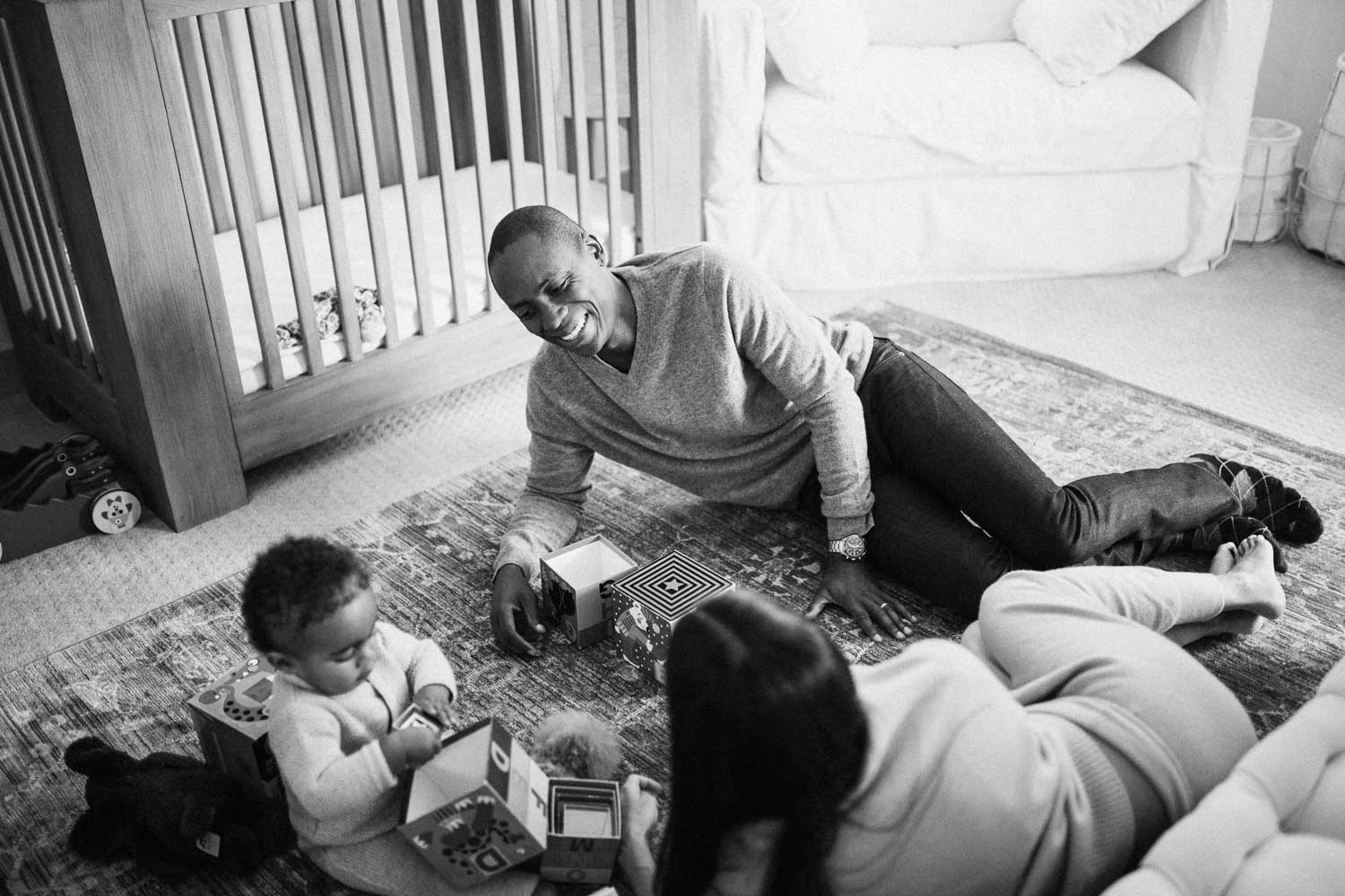 candid-black-and-white-precious-moment-of-parents-and-child-playing-with-toys-in-nursery-la-california