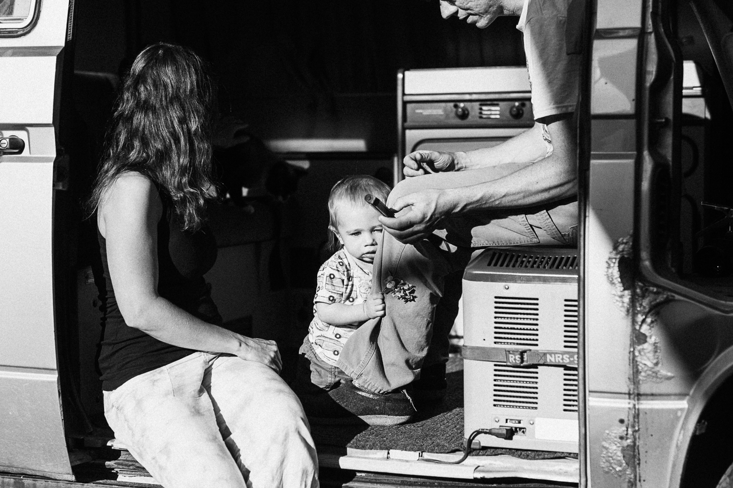 candid-artistic-black-and-white-photo-of-parents-and-child-siiting-in-van-during-in-home-session-with-jen-fairchild-photography