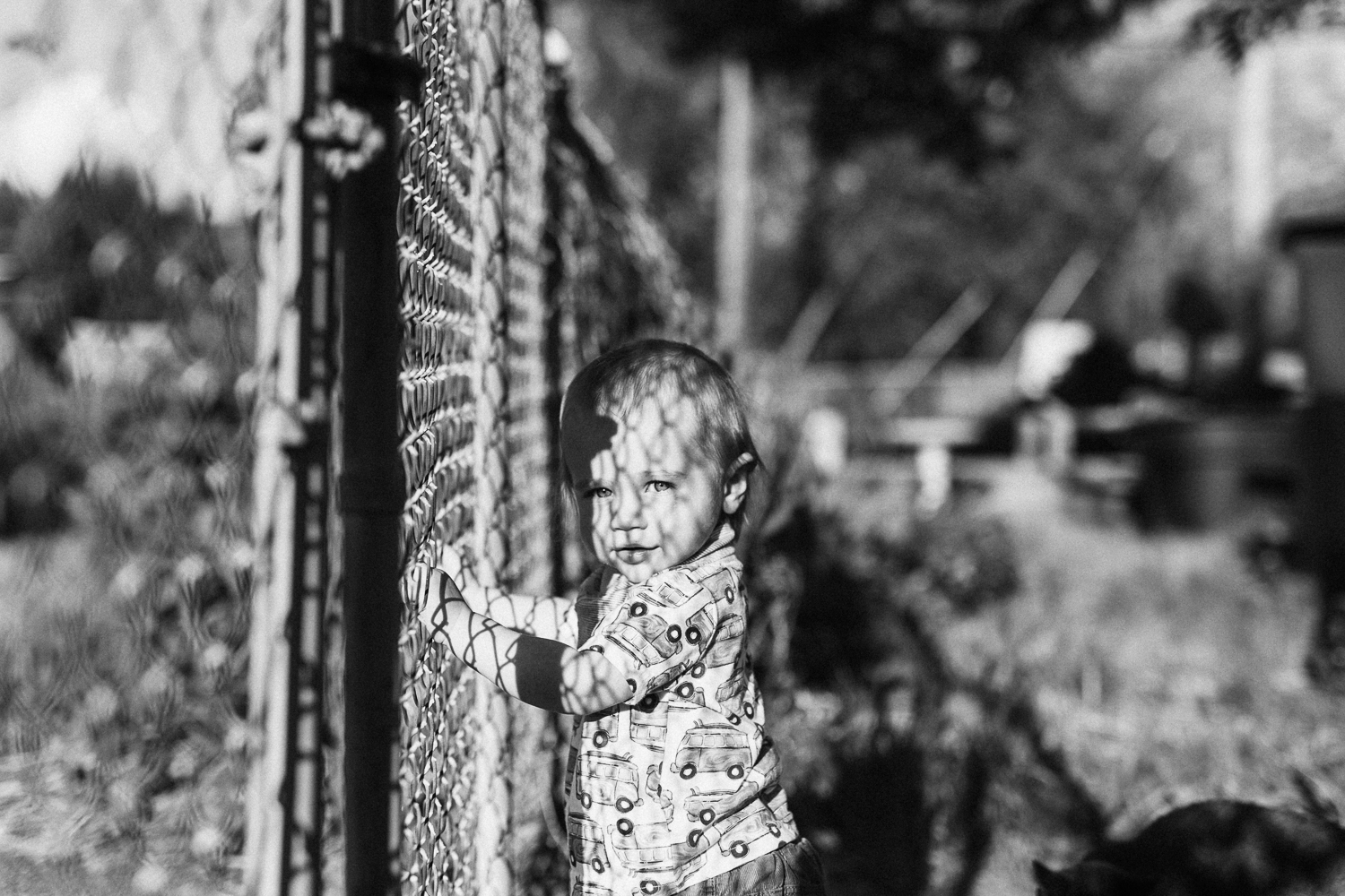 natural-and-artistic-black-and-white-fence-shadows-on-little-boys-face-slc-utah