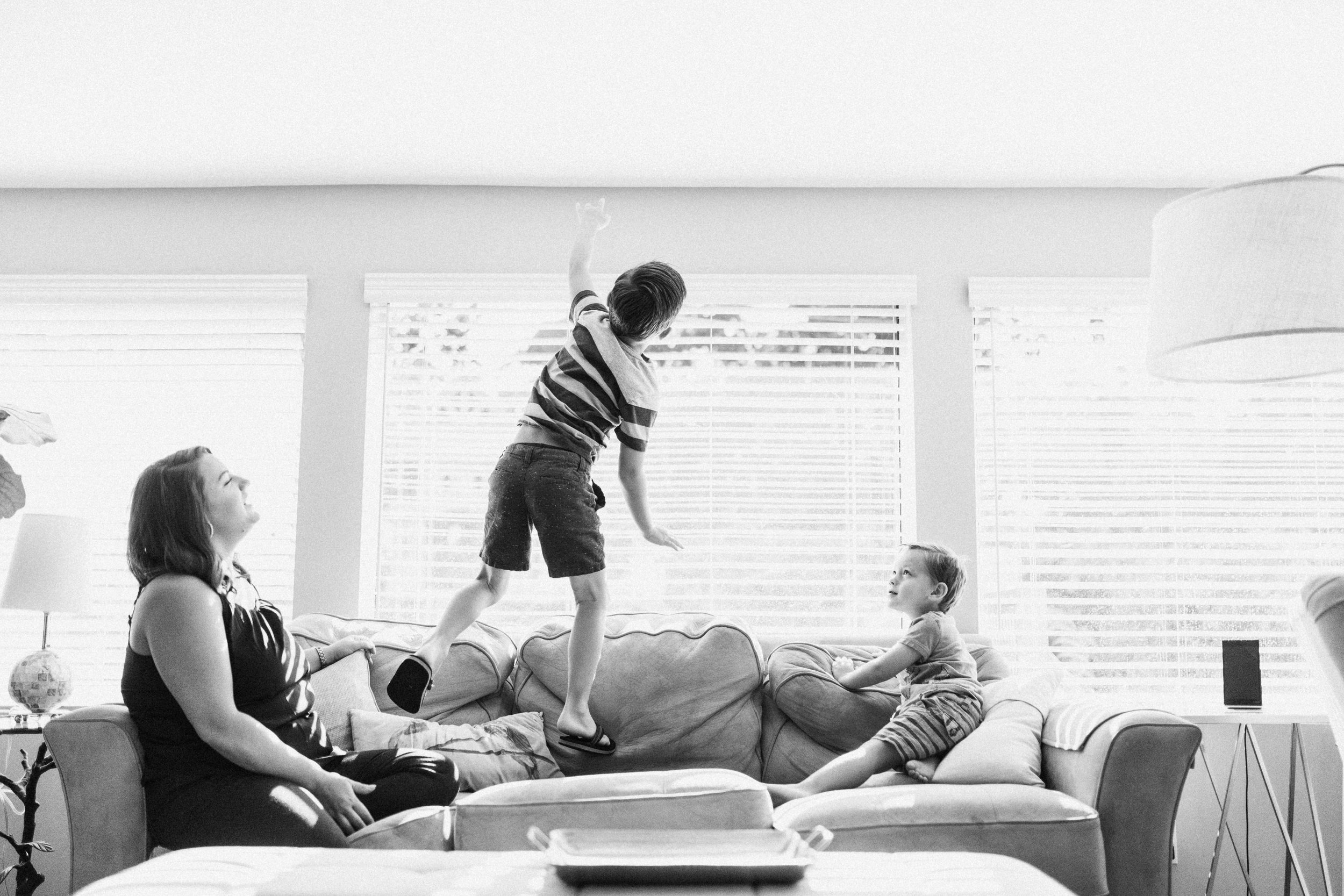 candid-black-and-white-photo-of-boys-playfully-jumping-on-couch-salt-lake-city-utah