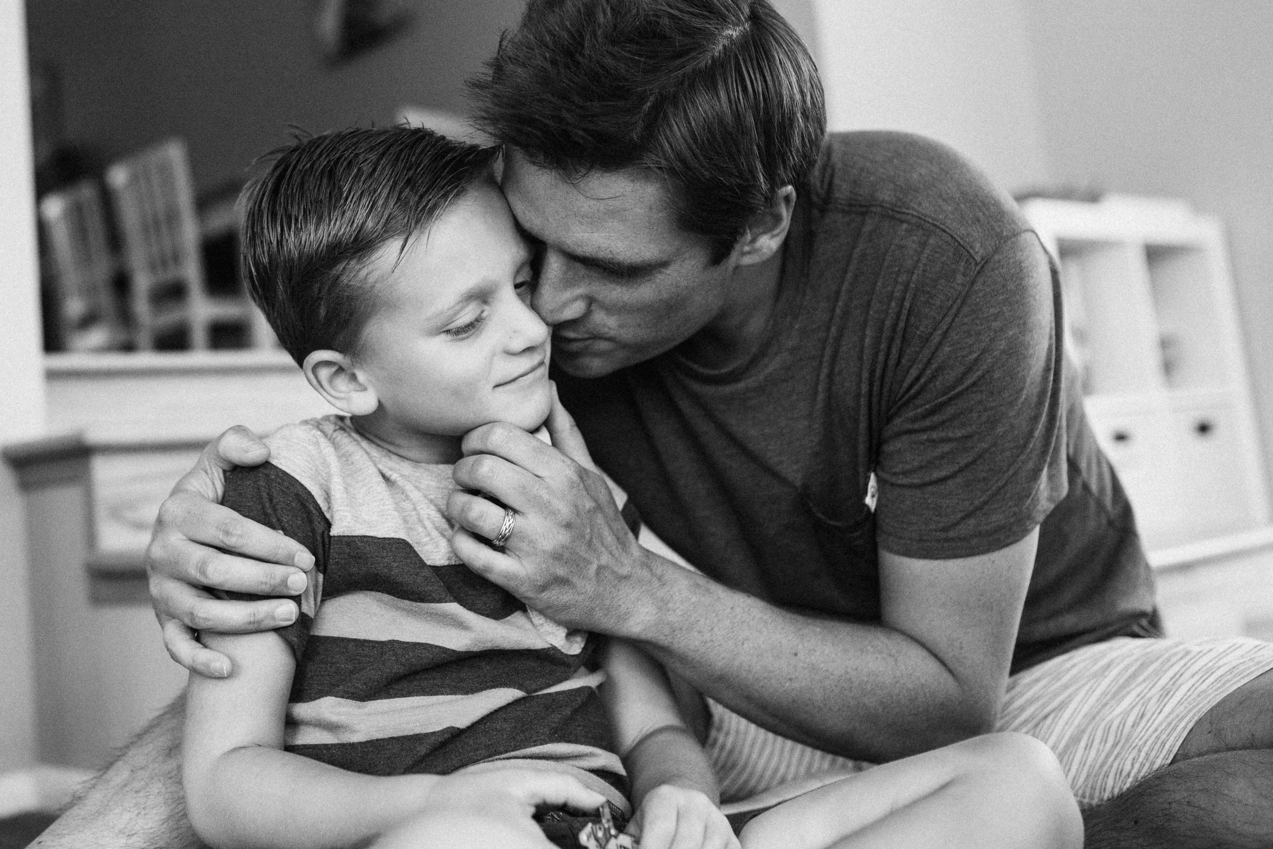 candid-black-and-white-intimate-loving-gesture-from-father-to-son-sugarhouse-utah