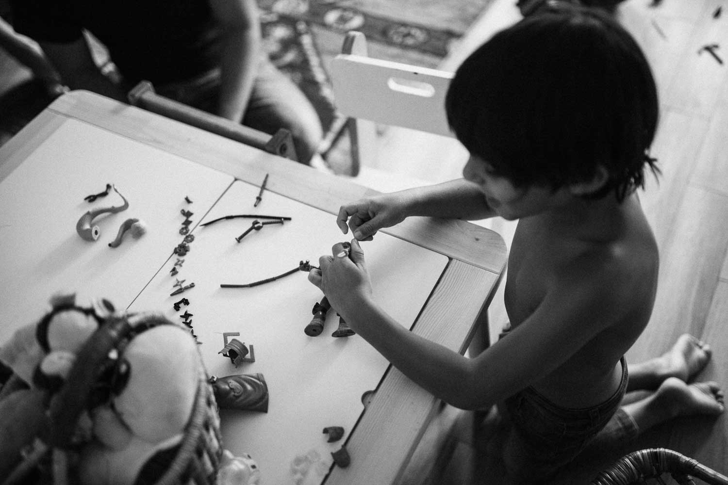 candid-black-and-white-photo-of-little-boy-playing-with-toys-ny-new-york-city