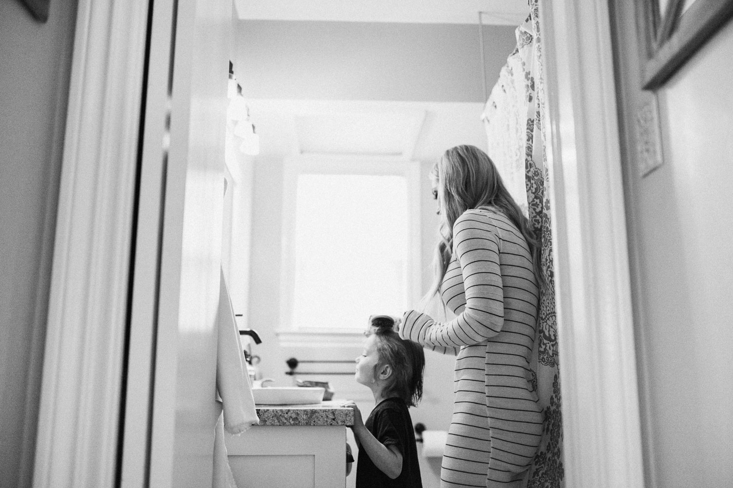 candid-black-and-white-photo-mother-brushing-childs-hair-bountiful-utah