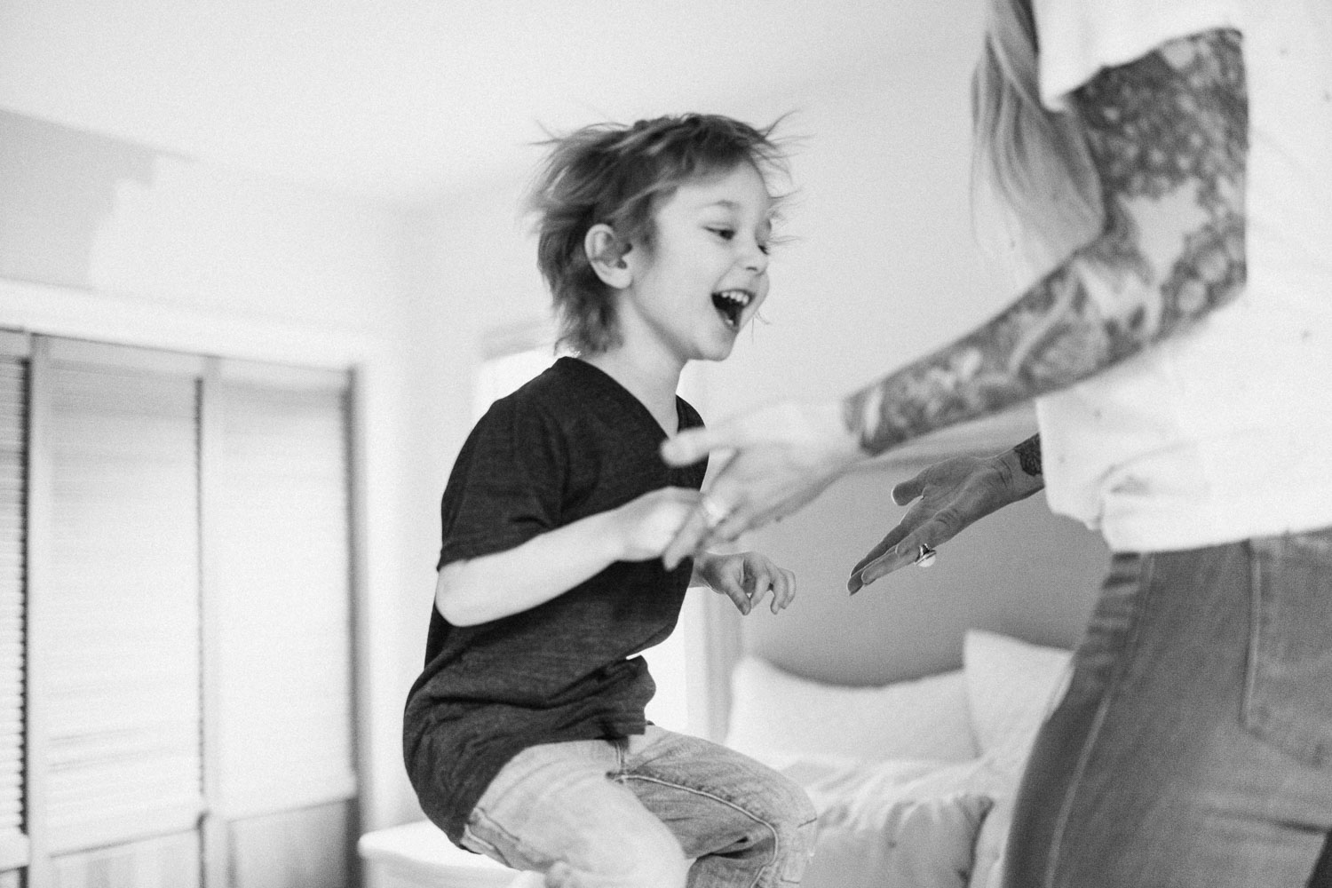 candid-photo-of-family-at-home-jumping-on-bed-draper-utah