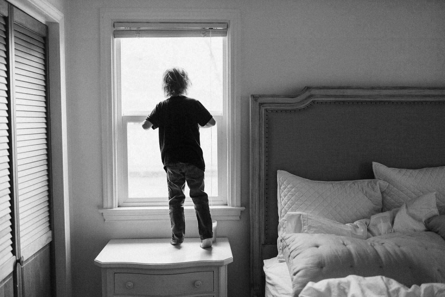 candid-black-and-white-photo-boy-looking-out-window-slc-utah