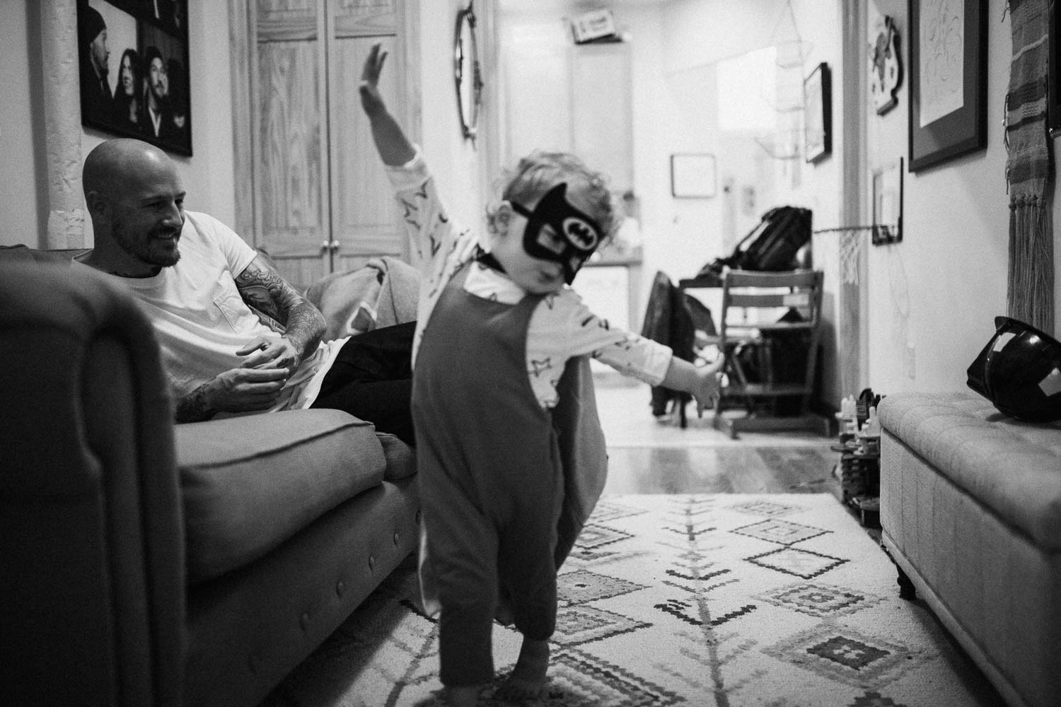 candid-black-and-white-photo-little-boy-in-batman-costume-slc-utah